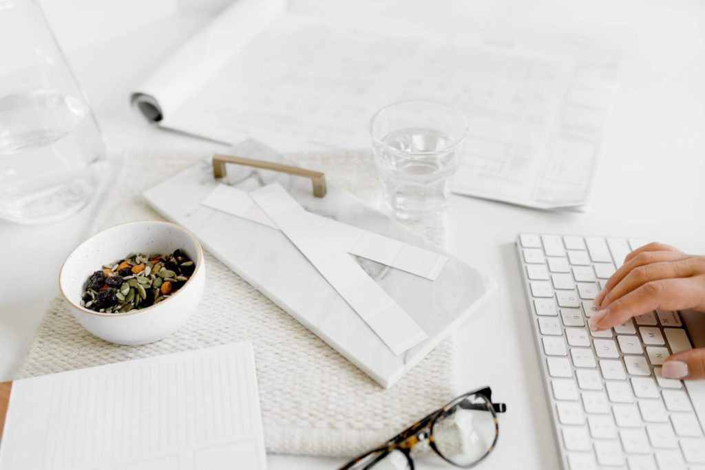 White flaylay with hands typing on a keyboard and a small salad bowl | How to start a blog and make money