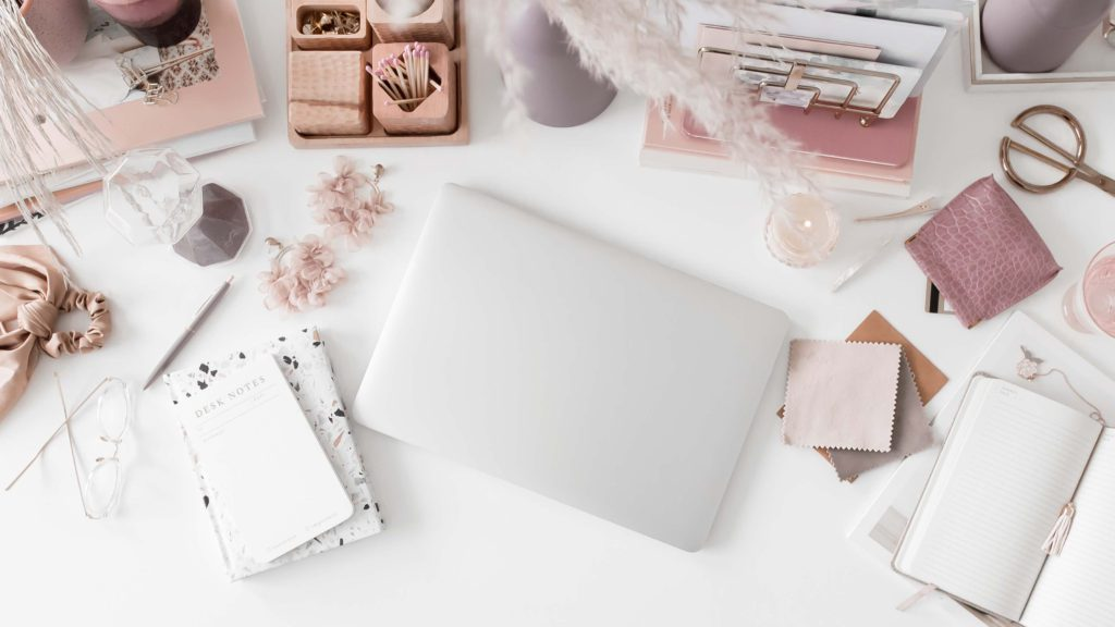 Desk flatlay in blush tones with a laptop