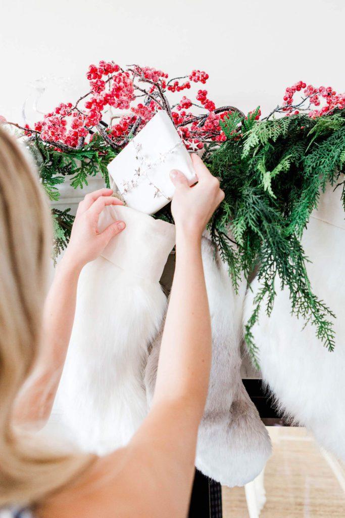 Woman putting a Christmas card inside a Christmas stocking | 2020 Christmas Bucket List Ideas