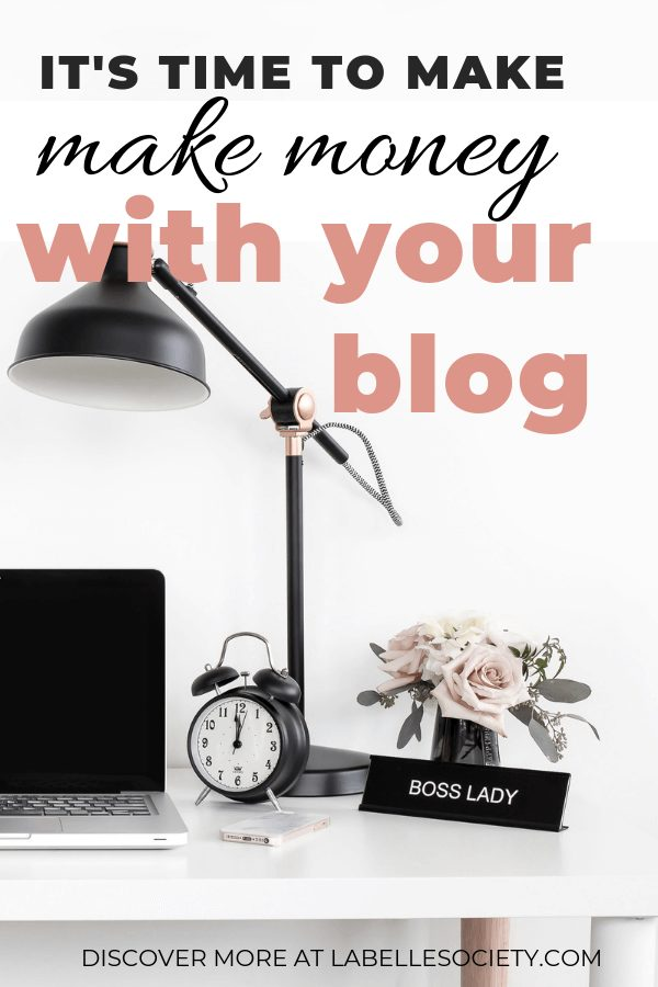 desk with a laptopt and a clock and a sign written boss lady in front of some flowers.