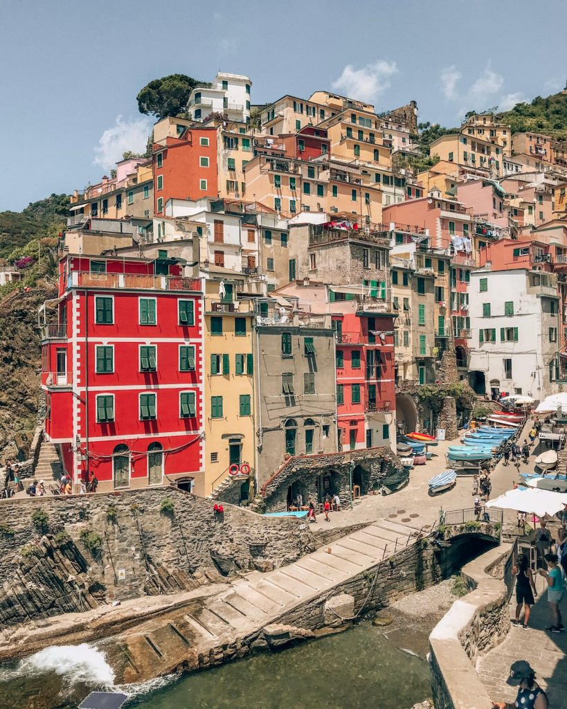 Riomaggiore in Cinque Terre seen from afar with its iconic red building facade