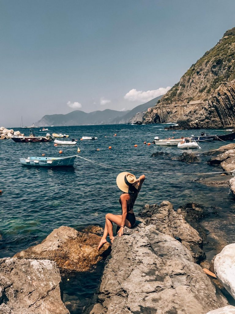 Girl sitting in a rock in Riomaggiore, a village located in Cinque Terre in Italy, during summer.