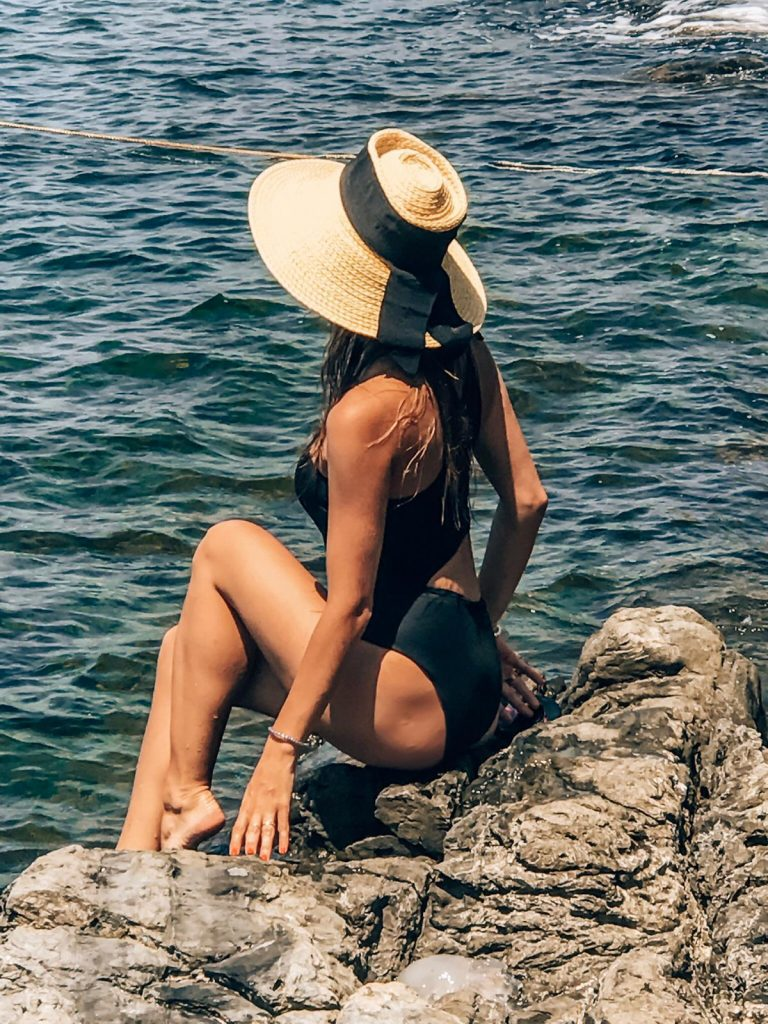 Ana Palombini sitting on a rock in Riomaggiore during summer in Italy