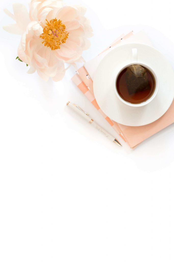 flatlay of a coffee cup with a pink flower  Five Dimensions of Self-Care