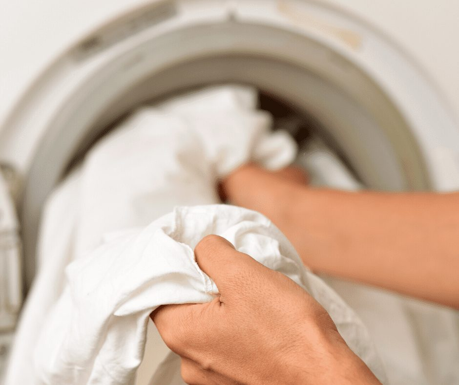 Pair of hands taking out white linen from the laundry machine | | Ways to Organize Your Home