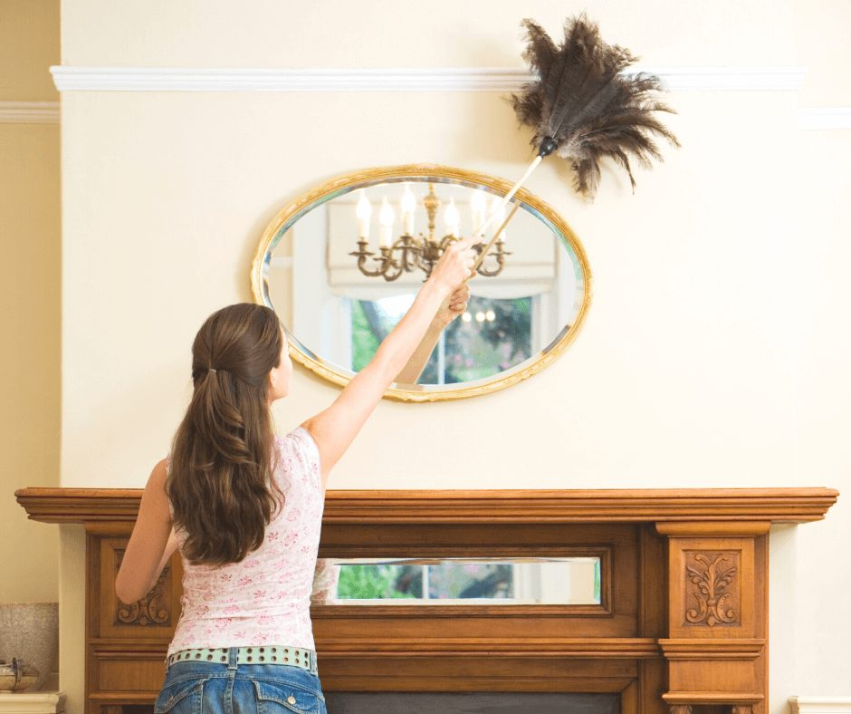 Girl with her back to camera dusting the living room ceiling