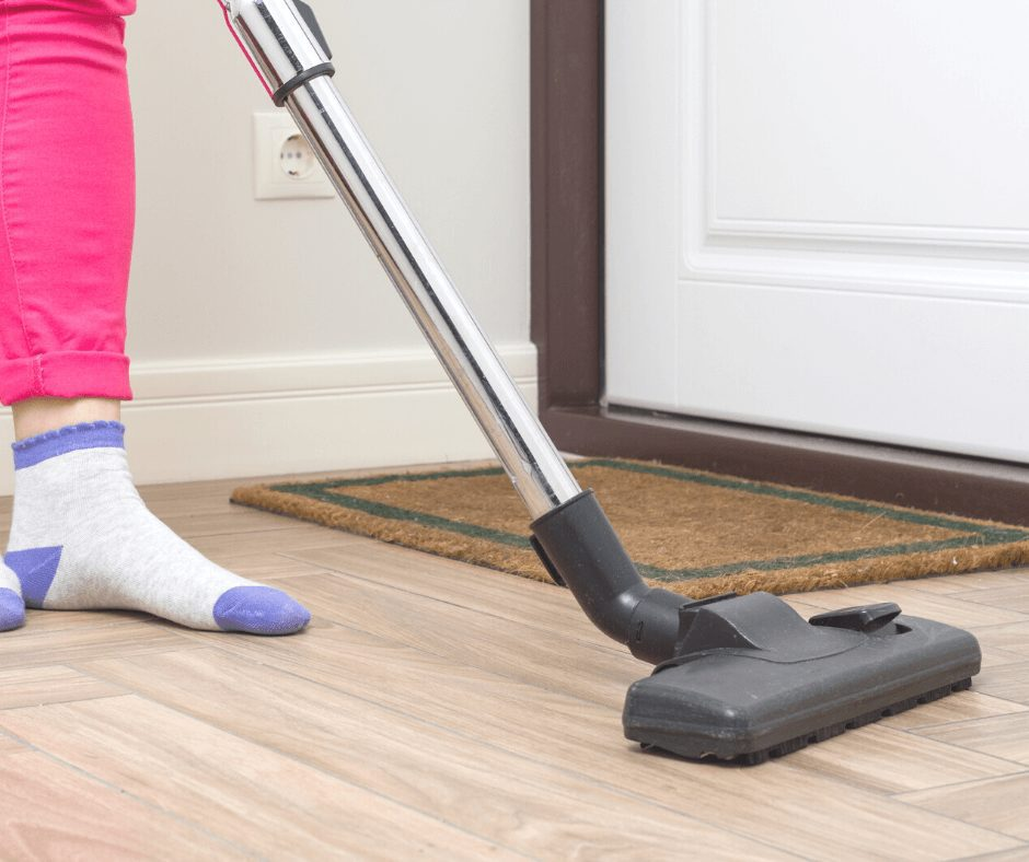 legs wearing pink jeans and socks vacuuming the living room entrance