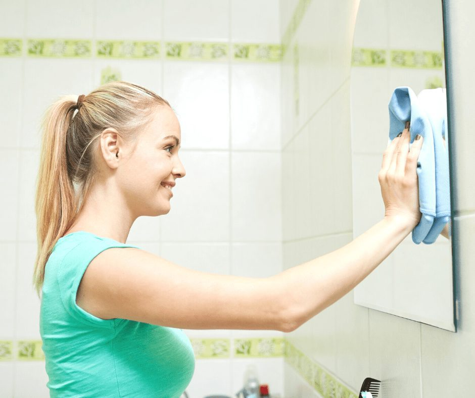 Blonde girl wearing green shirt smiling while cleaning bathroom mirror