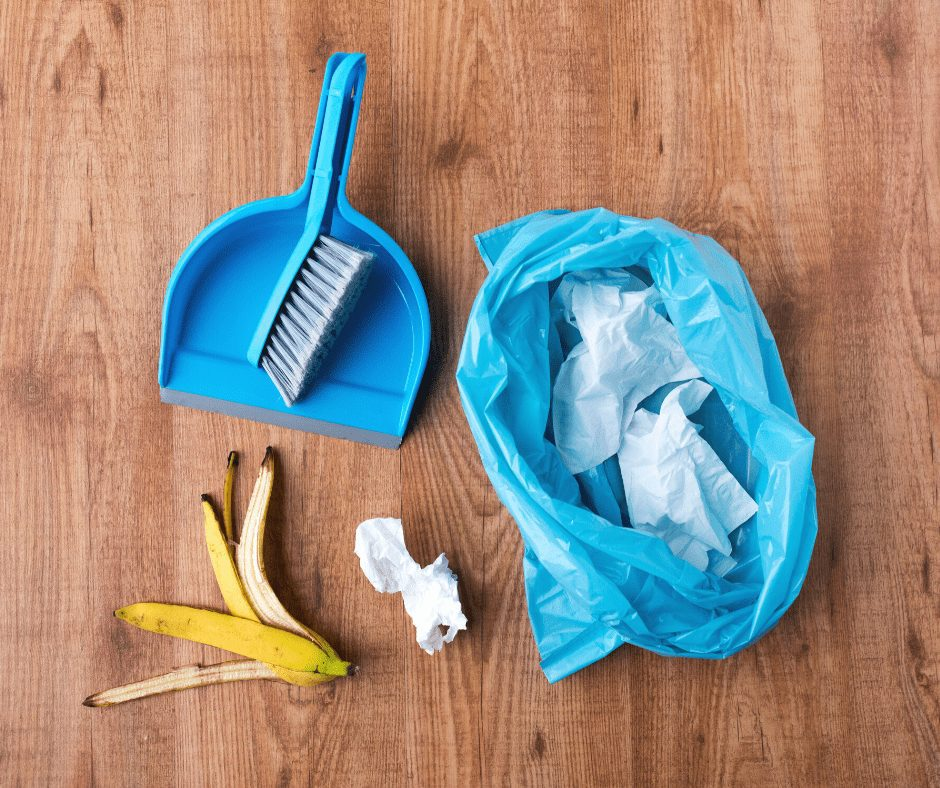 Waste flat lay: blue garbage bag, banana peel, toilet paper and blue cleaning brush flat lay