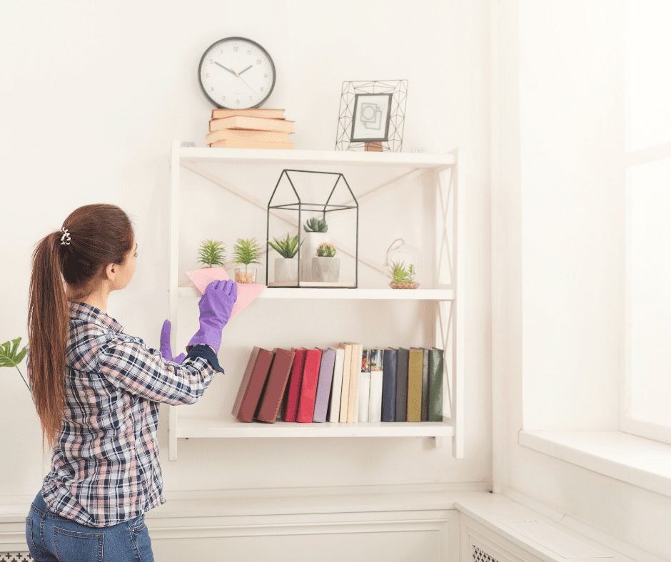 Brunette girl in a ponytail, wearing a checkered shirt and  with purple cleaning gloves, while cleaning the living room shelves.