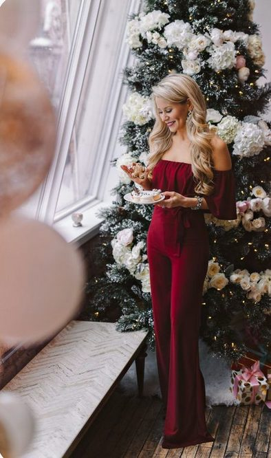 Girl wearing an All-Red Xmas Jumpsuit in front of a classy Christmas tree