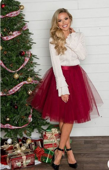 Girl wearing a Cute Red Ballerina Skirt in front of a Christmas tree
