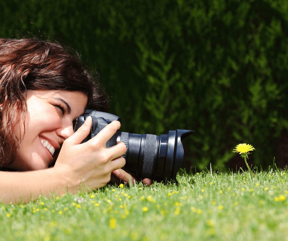 Girl taking photo of a small yellow flower