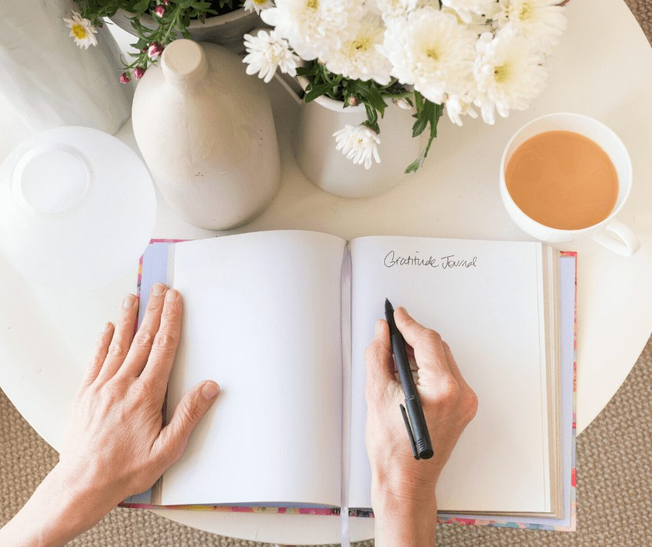 Flat lay of hands writing in a journal