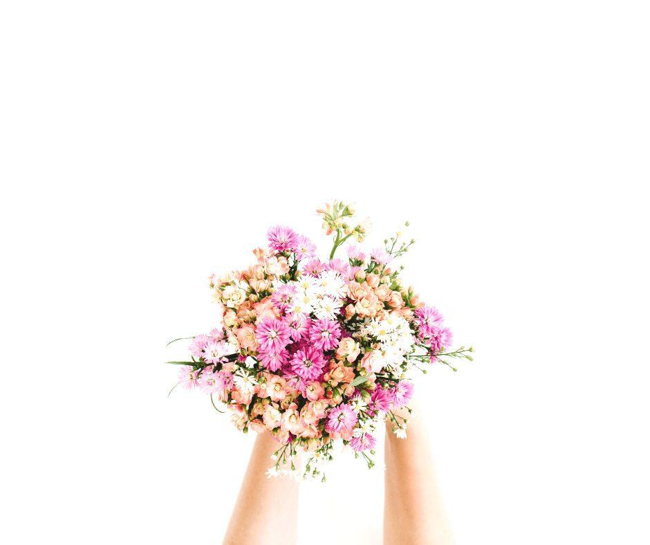 hands holding a pink bouquet
