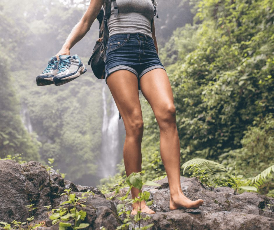 girl wearing shorts and holding her sneakers hiking.Being outdoors is one of the great Hobbies for Women to Start