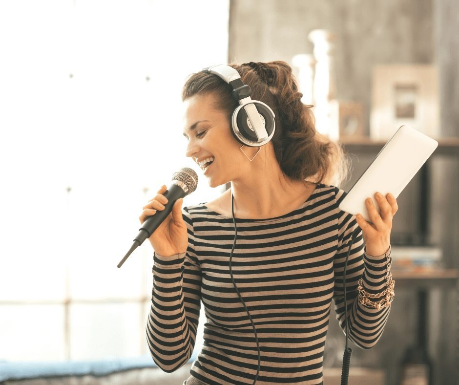 Girl wearing a black striped shirt singing into a mic