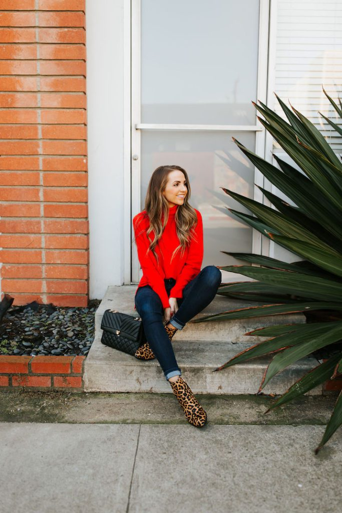 Girl wearing red accents jumper, jeans and leopard boots sitting outside