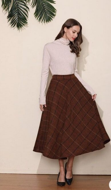 Elegant fall outfits: woman wearing a Brown, wool midi skirt with long-sleeved cream blouse.
