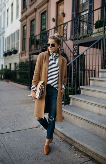 Elegant fall outfits: woman wearing a stripped shirt with tight jeans and a long, light camel coat with matching camel loafers