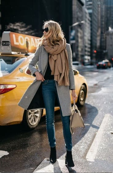 Elegant fall outfits: woman wearing a Jeans with black shirt and black boots, midi grey coat and a cream scarf.