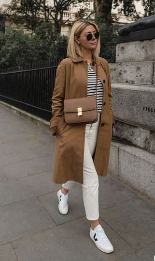 woman wearing a Striped shirt with white jeans and white sneakers, midi camel coat