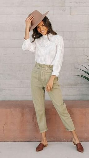 woman wearing a Light green pants, delicate white blouse and brown mules wit a cream Fall hat.