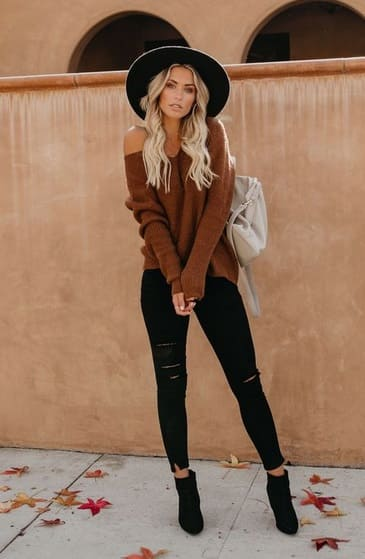woman wearing a Black leggings with black ankle boots and a matching black hat. Break the monochrome with a brown sweater and cream backpack.