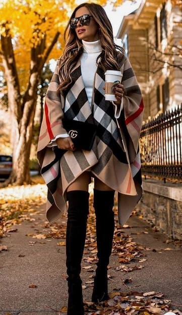 woman wearing a Burberry coat with over-the-knee black boots and black Gucci bag