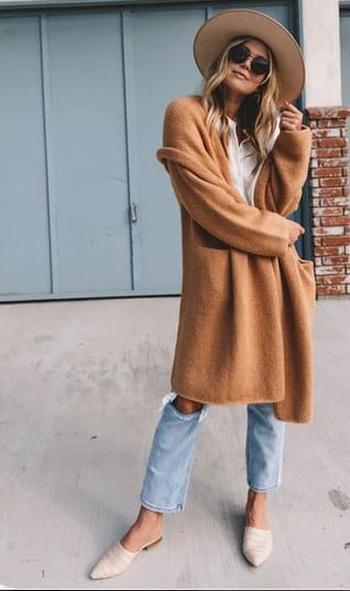 woman wearing a Comfy jeans and oversized camel cardigan and white, flat mules