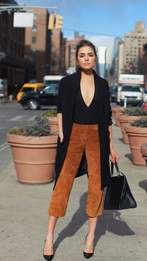 Elegant fall outfits: woman wearing a Camel midi pants with black shirt, black coat, back shoes and black bag