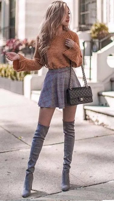 woman wearing a Cute Fall Outfit with short skirt and camel sweater, holding a handbag