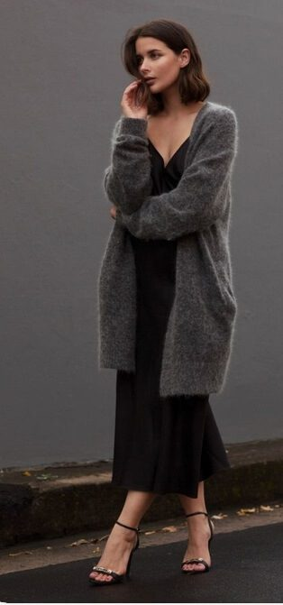 woman wearing a Black silk dress with oversized grey wool cardigan and delicate black sandals.