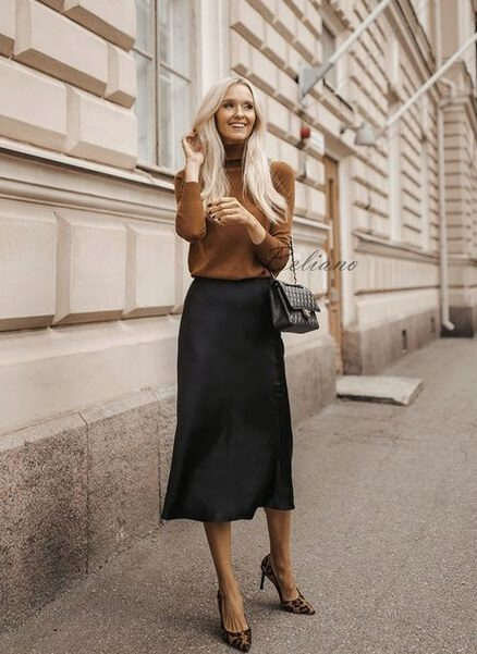 woman wearing Midi black silk skirt and a camel, long-sleeved blouse and animal-printed escarpins (AKA pointy shoes).