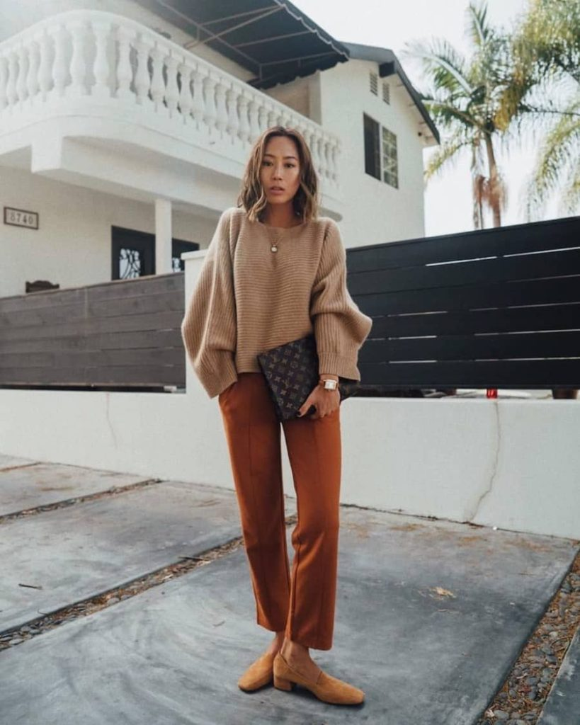 Elegant fall outfits: woman wearing a Monochromatic Outfit with camel pants and cream sweater