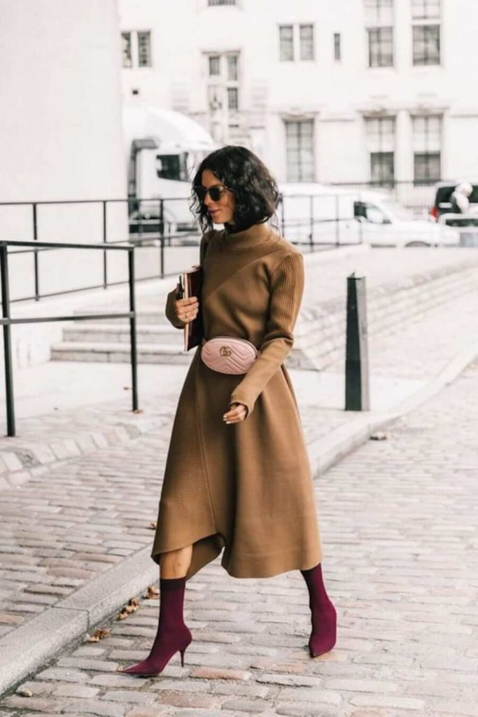 Elegant fall outfits: woman wearing a Camel Dress with Maroon Pointy Boots and a chic fanny pack