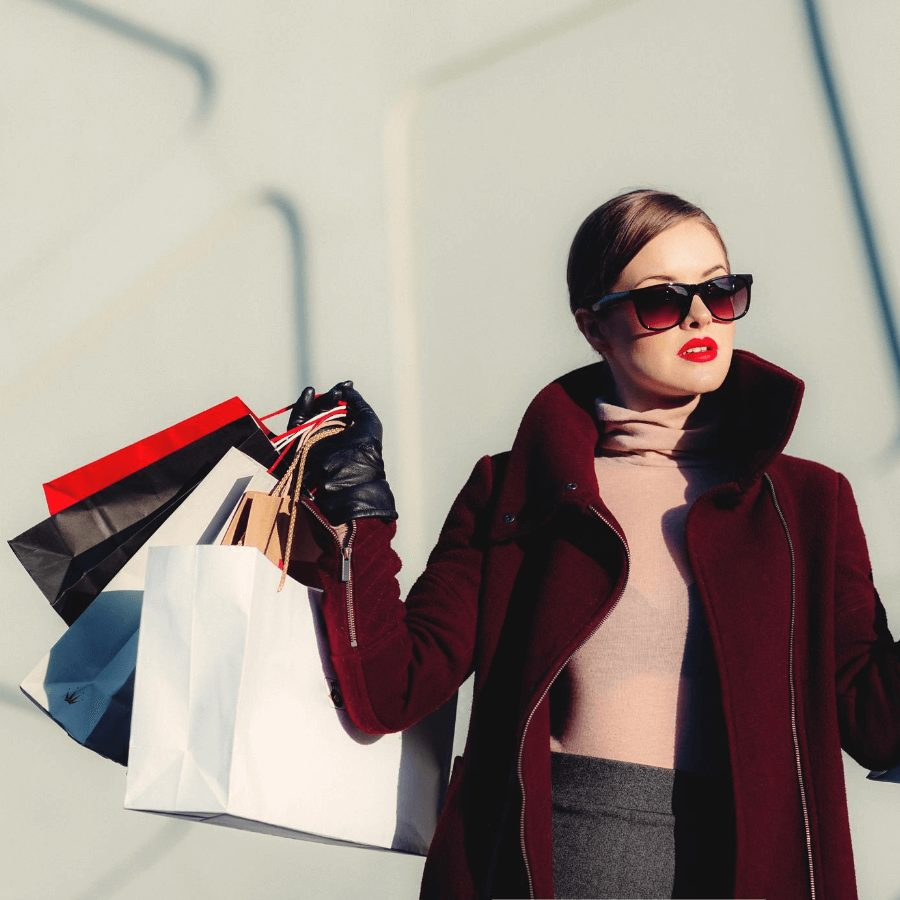 woman wearing sunglasses and maroon coat holding many shopping bags