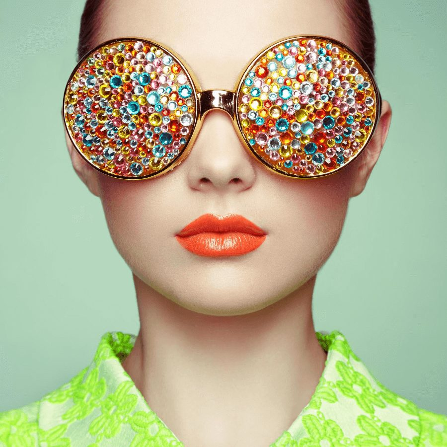 Girl wearing eyeglasses with colorful sparkles, orange lipstick and a green background