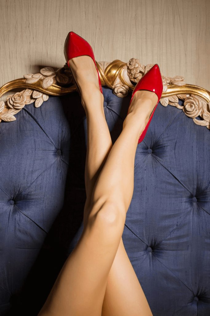 crossed legs facing up against a blue couch wearing red stilettos. | Fashion mistakes Parisian women never make