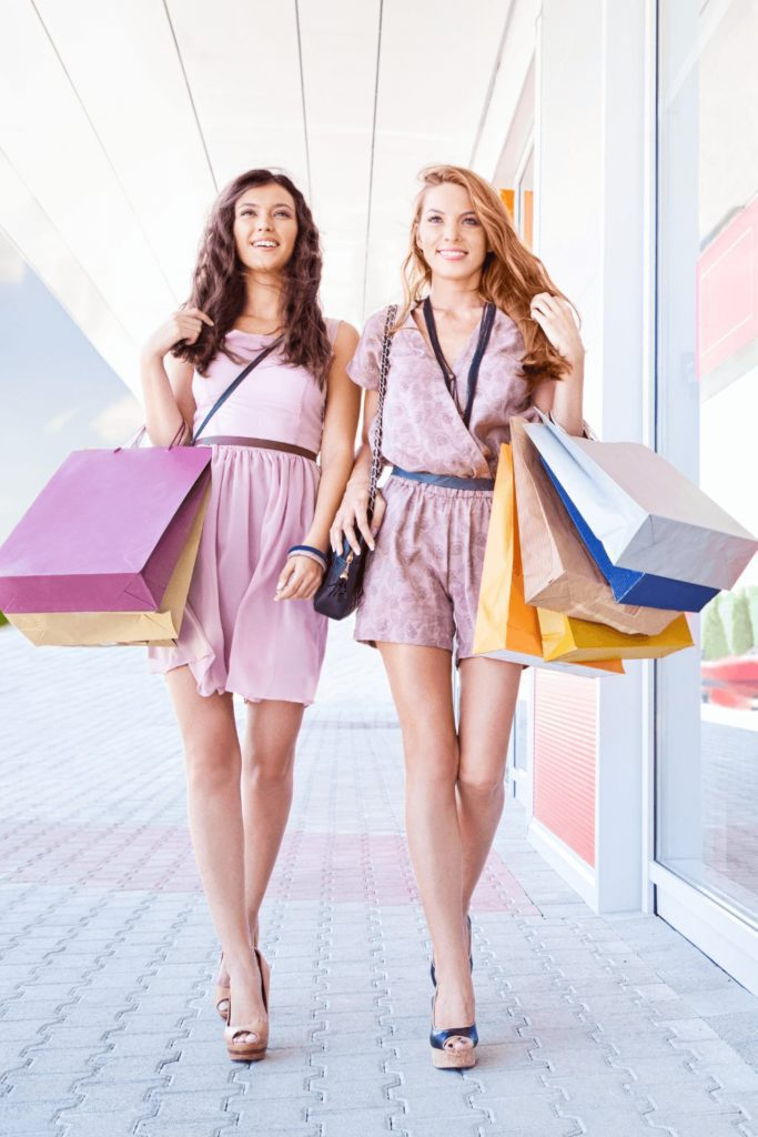 two smiling girls walking and carrying many shopping bags