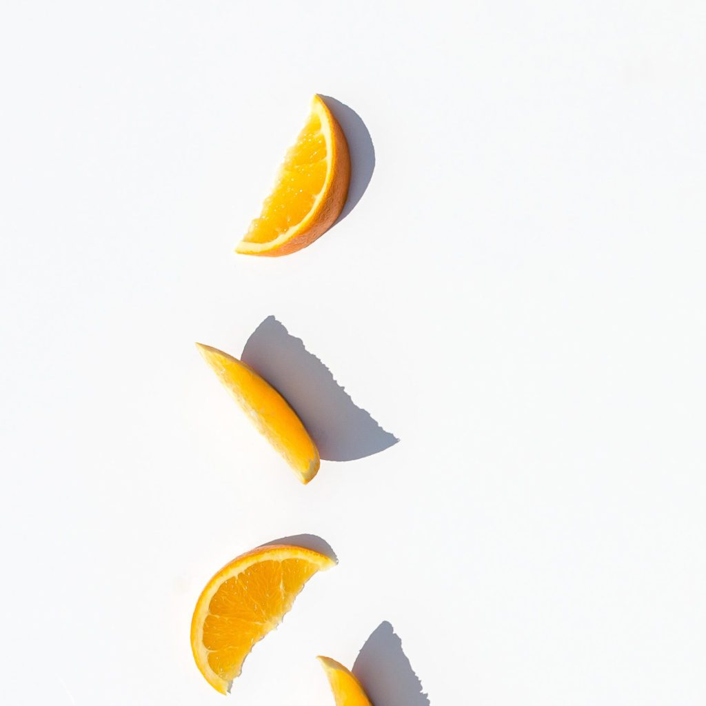 4 orange slices displayed on a white table