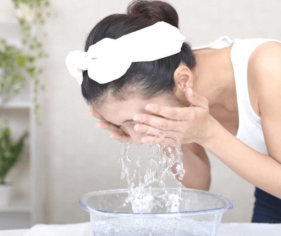 dark haired woman washing her face in a bowl of water