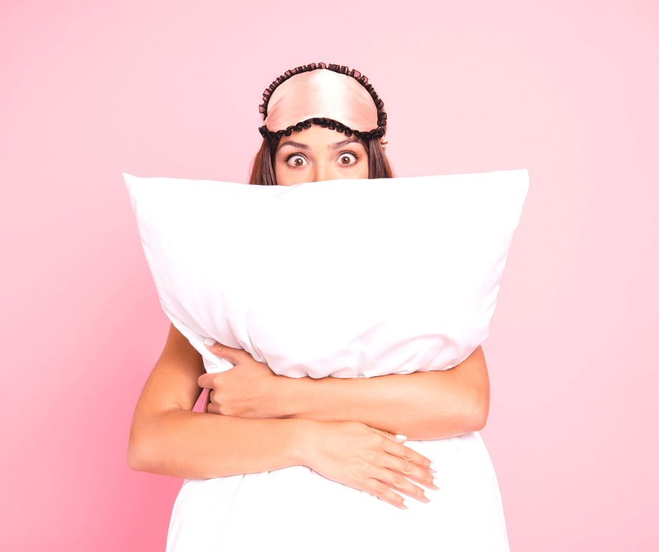 woman in a pink background wearing a pink sleep mask on her head and hugging a white pillow | bedtime beauty tips