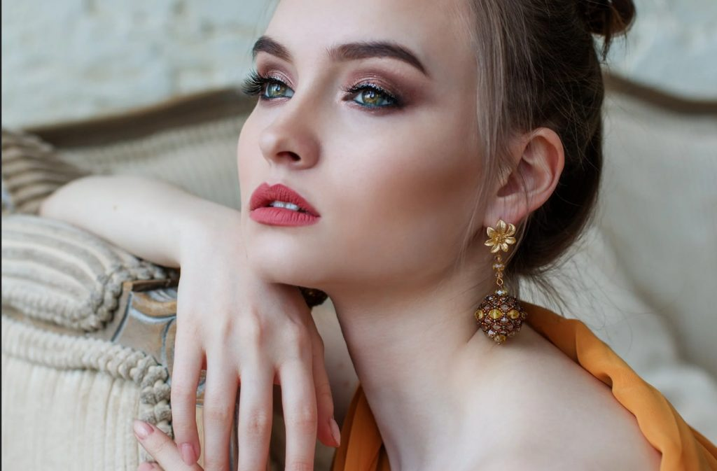 Elegant woman looking into the horizon using gold earrings