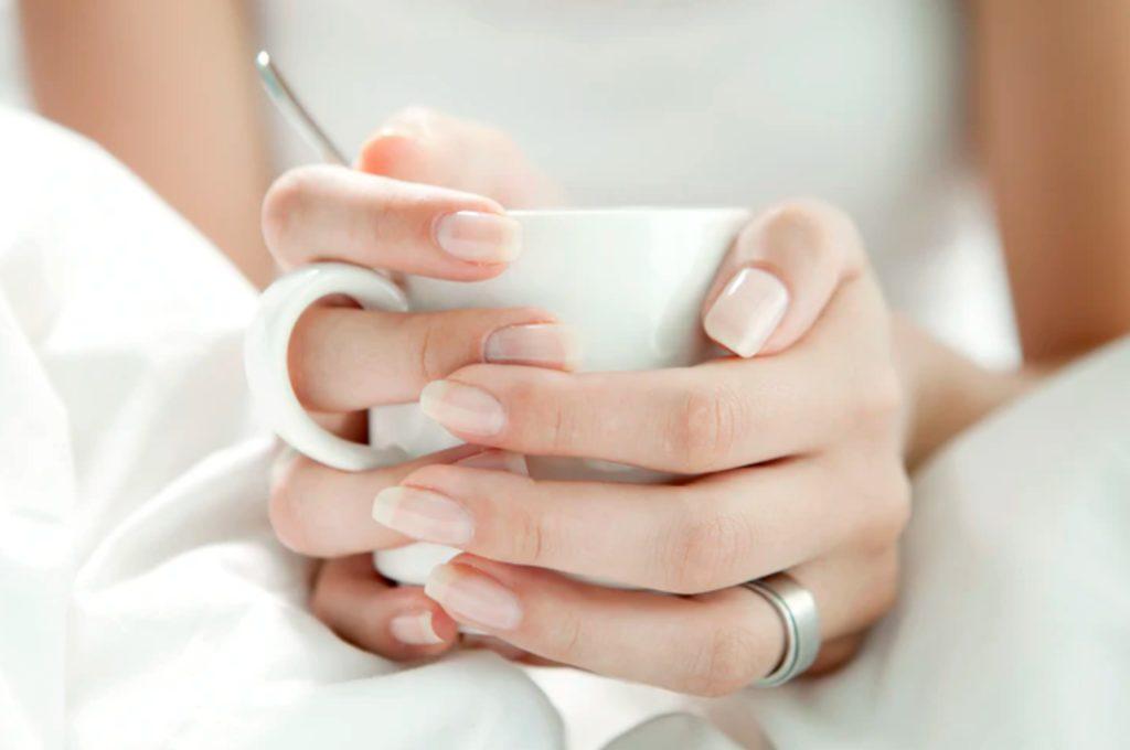woman's hands holding a white mug