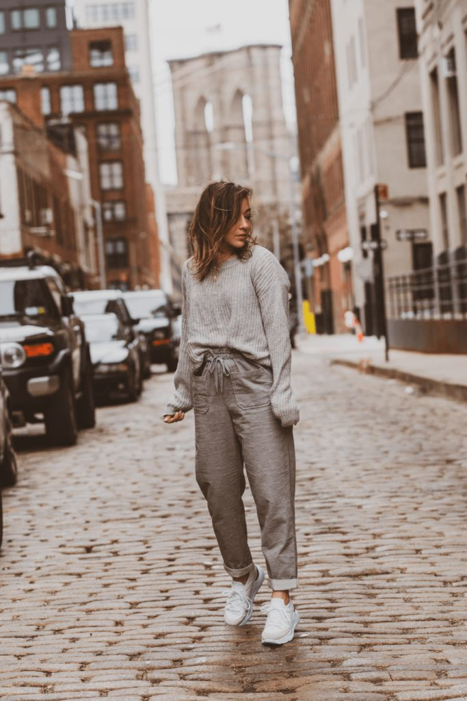 Girl wearing grey sweatpants and white sneakers outside is a fashion mistakes Parisian women wouldn't make