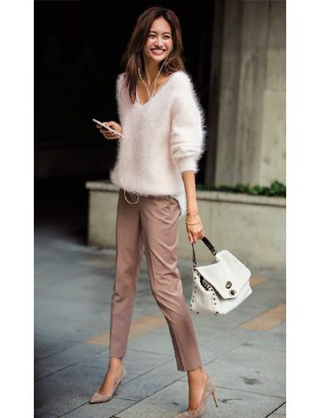 Brunette girl wearing a fluffy white sweater, cream pants and stilettos and holding a white handbag and mobile phone
