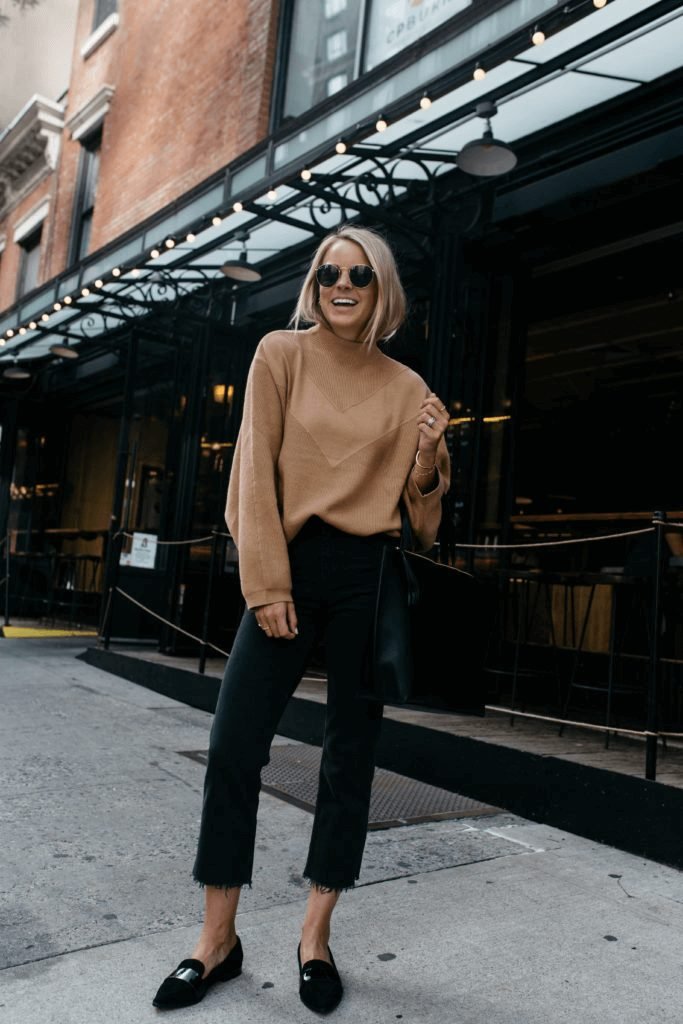 How to Dress Like an Italian Woman in Fall and Winter: blonde girl smilng wearing a camel shirt, black pants and sunglasses