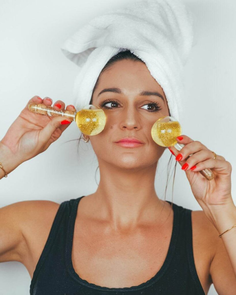 Ana Palombini with a white towel on her head and a black tank top utilizing Fraicheur Paris Ice Globes gold with glitter | Best ice globes for face