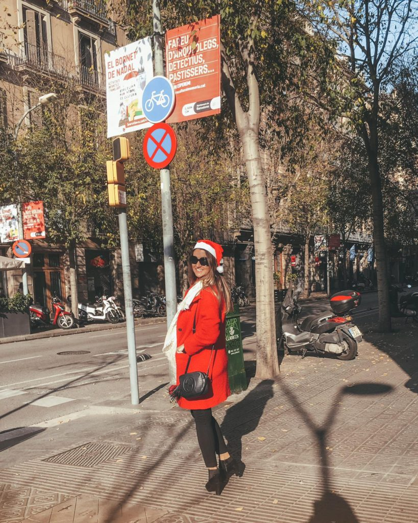 Girl wearing a red coat and a red Santa hat in the streets of Barcelona on Christmas day
